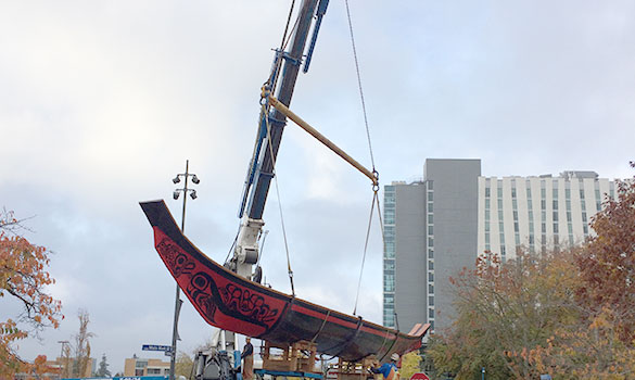 crane and rigging moving large canoe